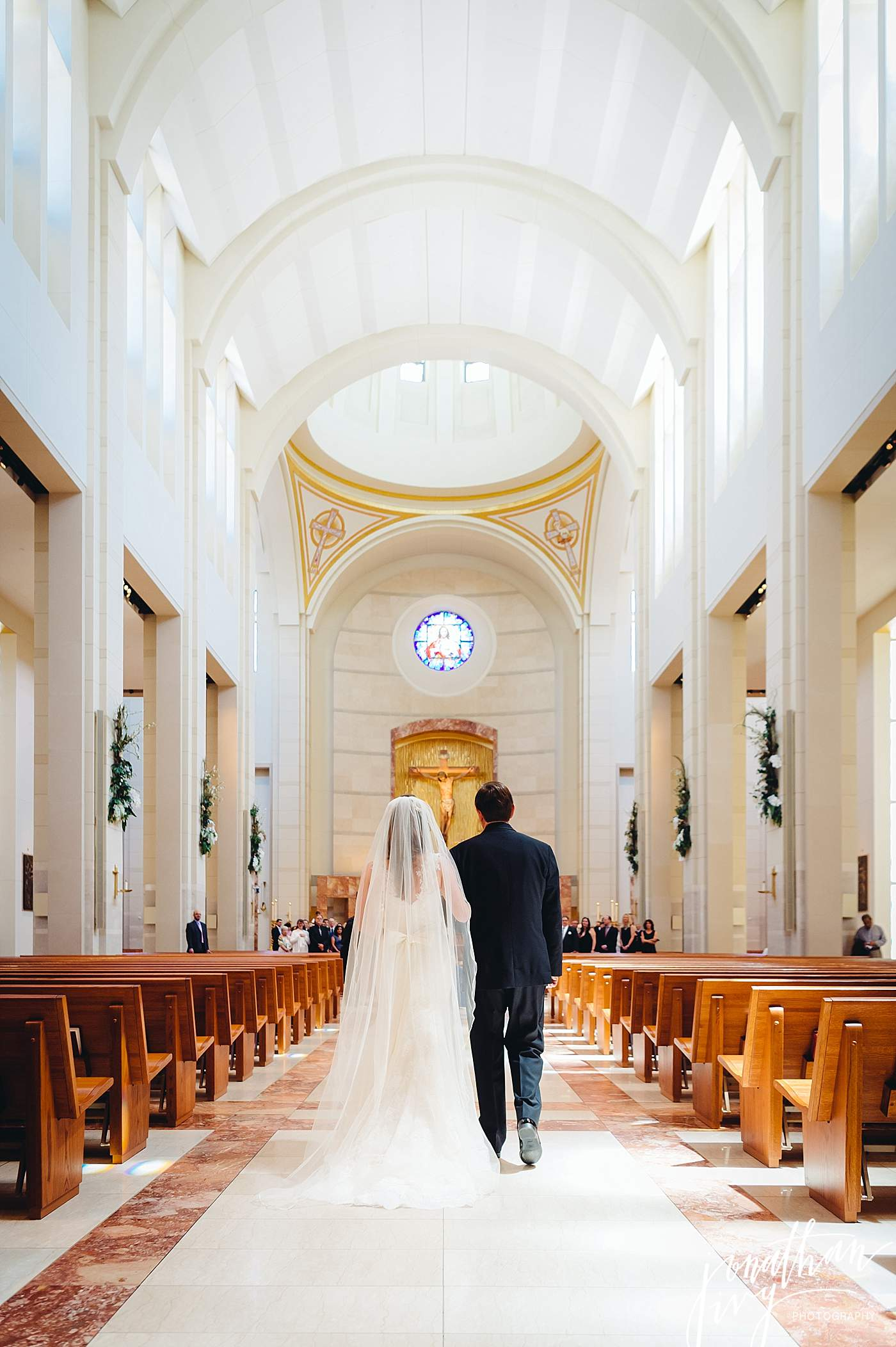 Bride walking down chapel aisle