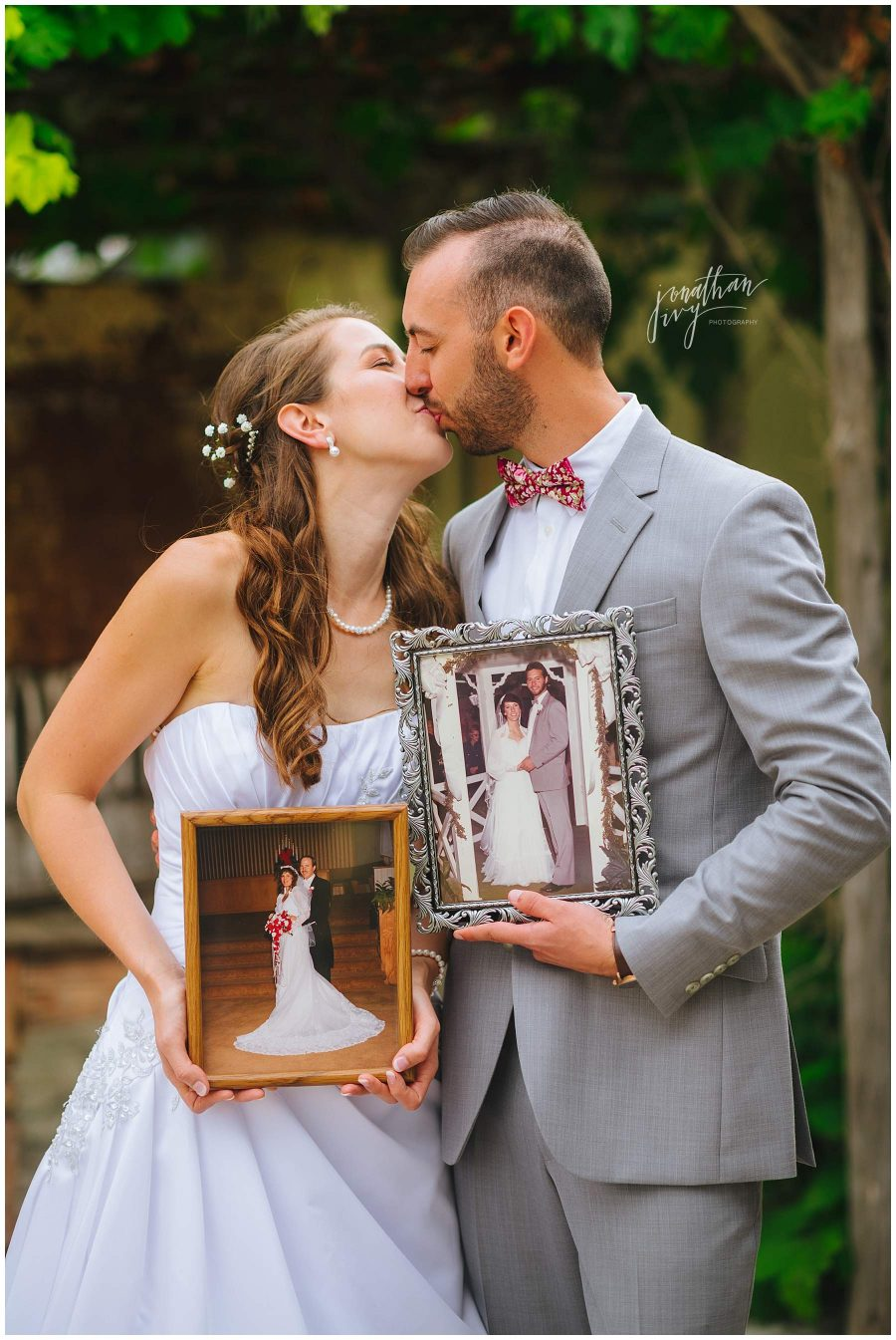 bride and groom holding pictures of family